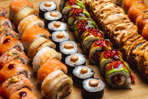 Sushi de vista lateral conjunto rolo de filadélfia com salmão e conger ell maki dragão rolo e rolo quente em uma placa