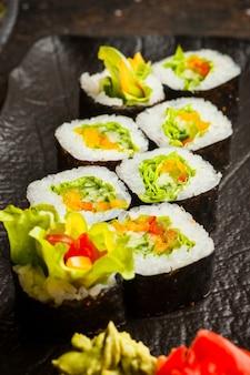 Sushi de vista lateral definido no prato escuro
