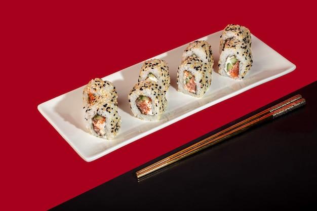 Sushi define nigiri, uramaki, califórnia, filadélfia, em um prato branco. sobre um fundo de cor vermelha. copie o espaço.