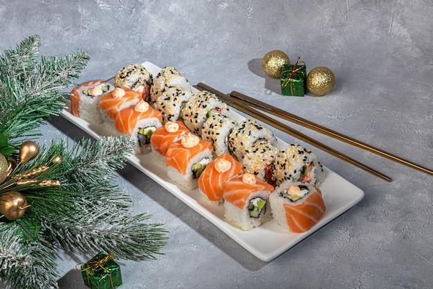 Sushi define uramaki, califórnia, filadélfia, em um prato branco. ano novo e conceito festivo. sobre um fundo cinza claro. copie o espaço.