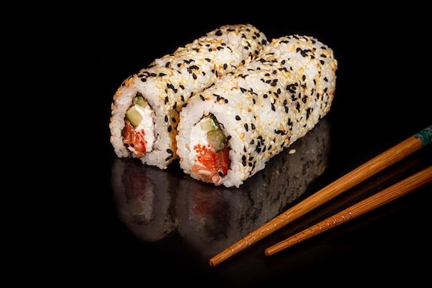 Sushi define uramaki, califórnia, filadélfia, em um prato branco. conceito festivo, ano novo. contra um fundo escuro reflexivo. copie o espaço