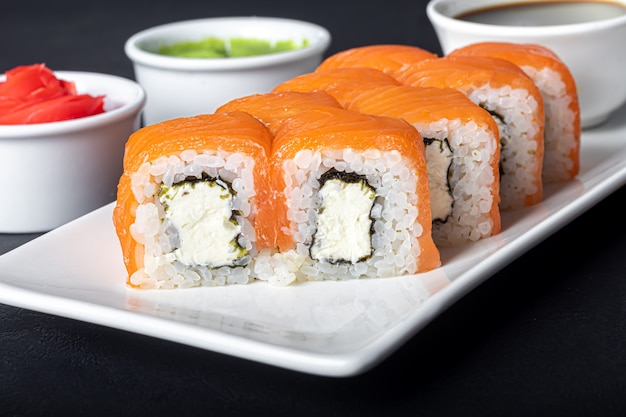 Sushi define uramaki, califórnia, filadélfia, em um prato branco. gengibre e wasabi próximos.