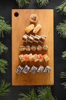 Sushi definido como árvore de natal servido na tábua de madeira como decoração de natal em fundo preto. vista de cima. estilo liso leigo. vertical.