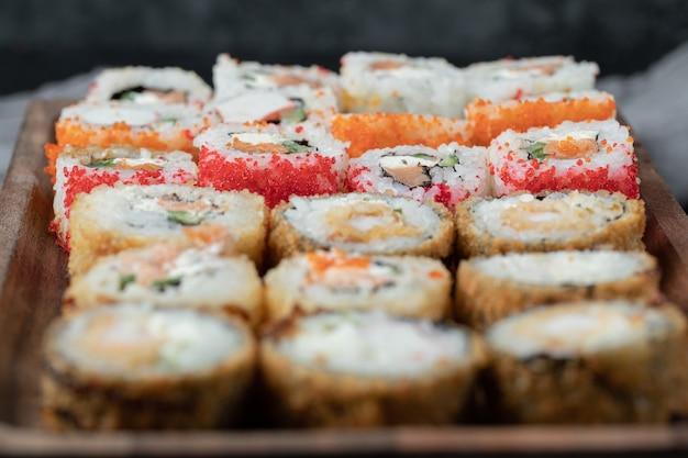 Sushi definido em uma placa de madeira com ingredientes misturados.