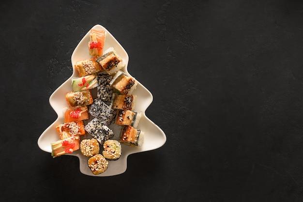 Sushi definido no prato como árvore de natal decorada com galhos de árvore do abeto no preto