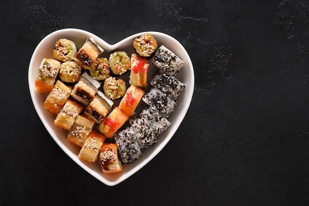 Sushi definido no prato como coração em fundo preto. conceito de amor por comida para o dia dos namorados