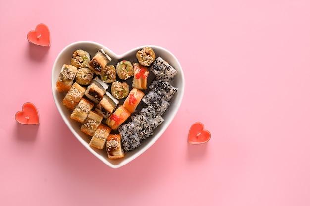 Sushi definido no prato como coração em fundo rosa. conceito de comida do dia dos namorados. vista de cima. espaço para texto. estilo flatlay.