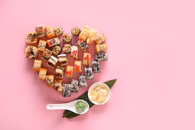 Sushi definido no prato como coração servido gengibre, wasabi em fundo rosa. conceito de comida do dia dos namorados. vista de cima. espaço para texto. estilo flatlay.