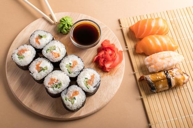 Sushi definir uramaki e rolos servidos na esteira de bambu e tábua de madeira