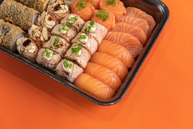 Sushi delicioso e bonito na mesa laranja