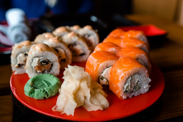 Sushi delicioso em uma placa e em um wasabi vermelhos.