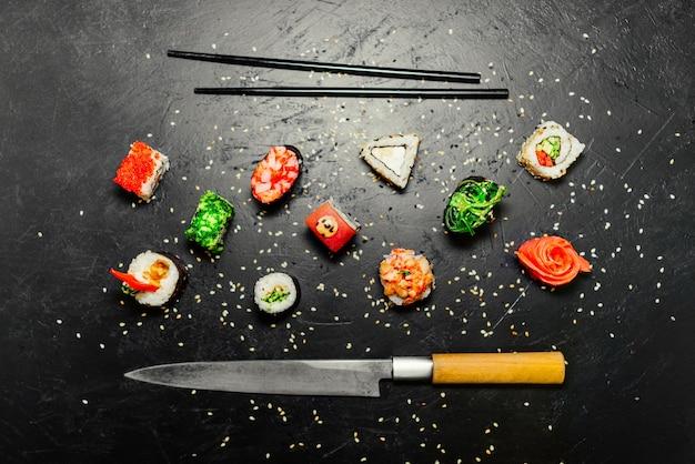 Sushi diferente com a faca japonesa no fundo de pedra preto da ardósia. sushi em uma mesa.