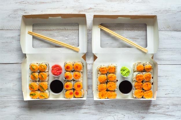 Sushi dois definido em uma caixa em uma mesa de madeira. comida de rua
