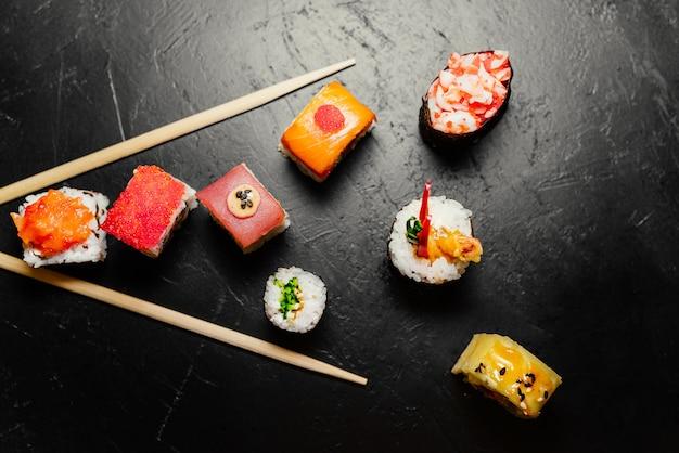 Sushi e chopsticks japoneses no fundo preto. rolinhos de sushi, nigiri, maki