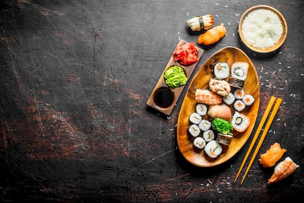 Sushi e pãezinhos em um prato com arroz cozido em uma tigela e os pauzinhos. na mesa rústica escura