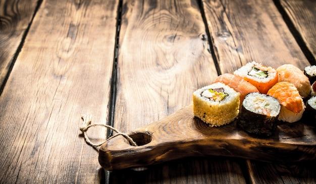 Sushi e pãezinhos no tabuleiro. em fundo de madeira.