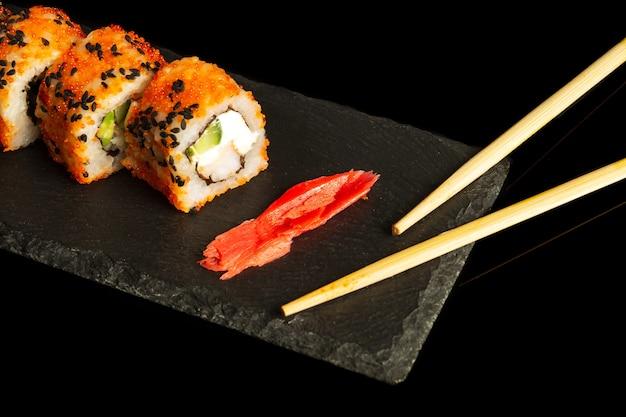 Sushi e pauzinhos tradicionais. filadélfia com salmão, abacate e queijo. cozinha japonesa em fundo preto.