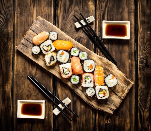 Sushi e rola de frutos do mar com molho de soja. em fundo de madeira.