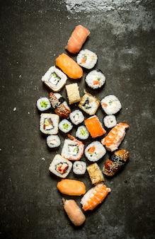 Sushi e rolinhos diferentes com frutos do mar na mesa de pedra