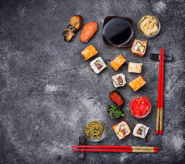 Sushi e rolo definido na mesa preta