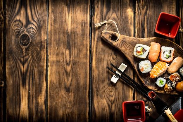 Sushi e rolos com chá de ervas. em uma mesa de madeira.