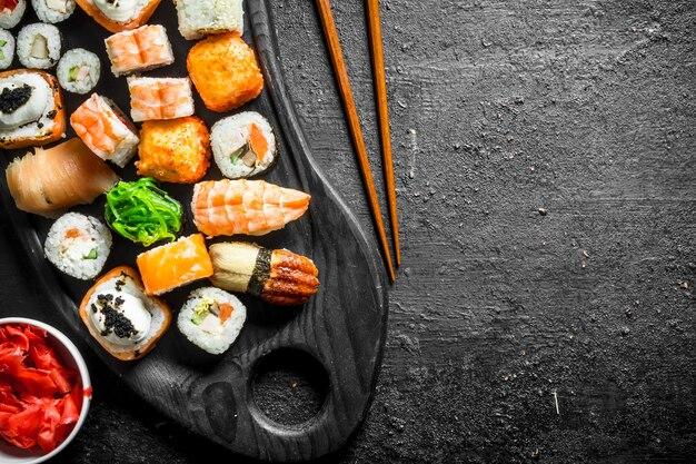 Sushi e rolos em uma tábua de cortar com gengibre e pauzinhos. em preto rústico
