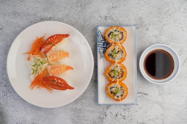 Sushi é um prato com molho sobre um piso de cimento branco.
