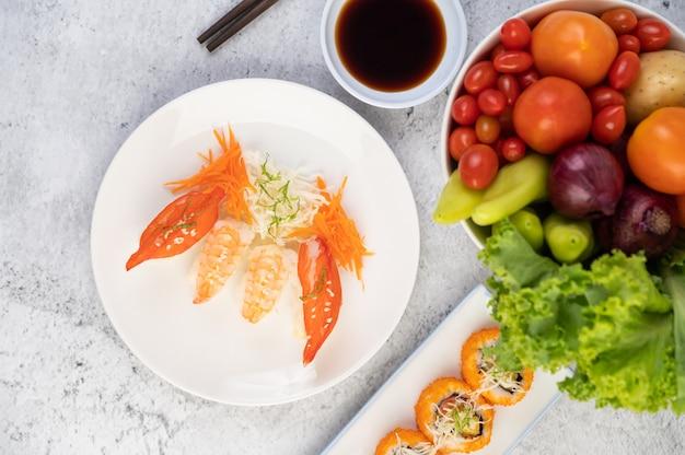 Sushi é um prato com pauzinhos e molho sobre um piso de cimento branco.