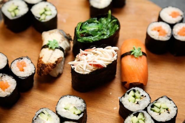 Sushi em conjunto com vários tipos de sushi pn mesa de madeira close-up vista