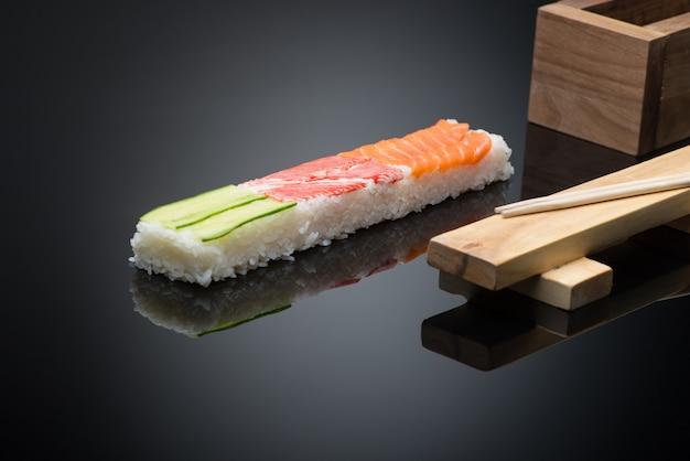 Sushi em fundo preto com pauzinhos. forma de prensa de madeira para fazer sushi