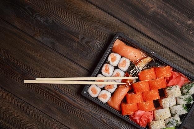 Sushi em prato preto e pauzinhos