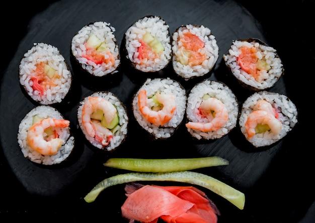Sushi em um grande prato preto.