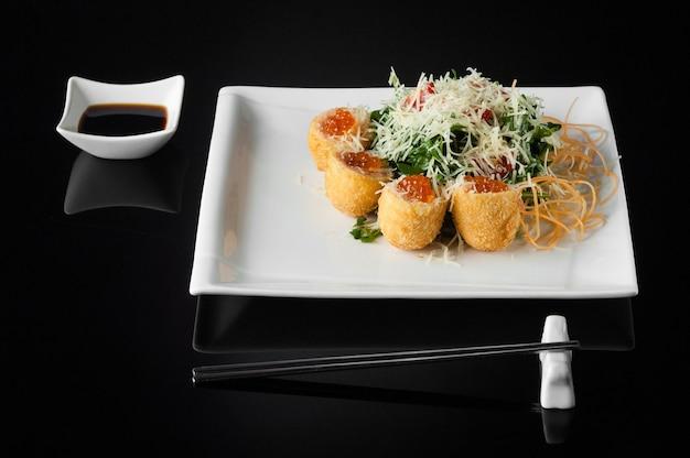Sushi em um prato branco com panela e pauzinhos em um fundo preto com reflexo