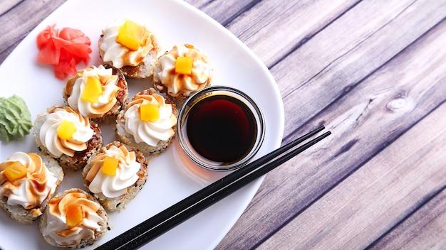 Sushi em um prato branco e textura de madeira