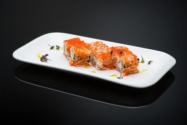 Sushi em um prato em um fundo preto com reflexão. rolo de peixe