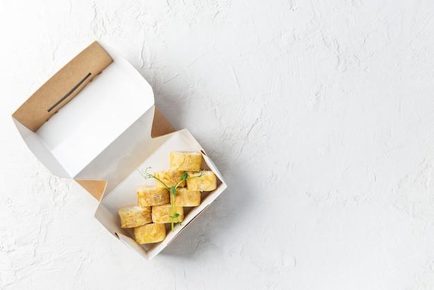 Sushi em uma caixa de papelão sobre um fundo claro.