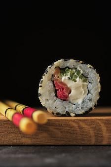 Sushi em uma placa de madeira. rolls com peixe em um fundo escuro.