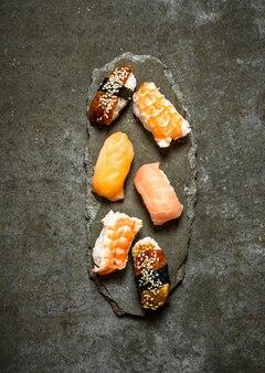 Sushi japonês com salmão, camarão e enguia na mesa de pedra