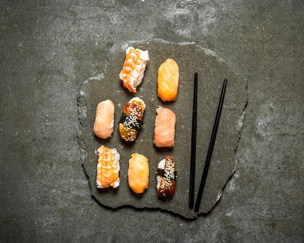 Sushi japonês com salmão, camarão e enguia. na mesa de pedra.
