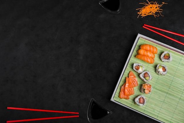 Sushi japonês fresco e delicioso com pauzinhos no fundo preto