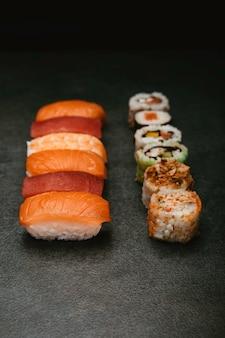 Sushi japonês variado com sabores diferentes em fundo preto