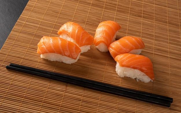 Sushi, lindo arranjo de sushi coberto de hashi em uma esteira de bambu