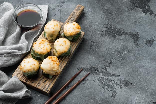 Sushi maki assado com conjunto de salmão, caranguejo, pepino, abacate, ovas de peixe voador e molho picante, em pedra cinza