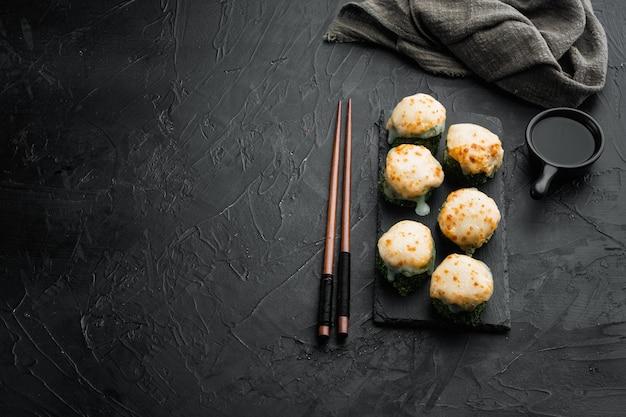 Sushi maki assado rola com salmão, caranguejo, pepino, abacate, ovas de peixe voador e conjunto de molho picante, em fundo de pedra preta, com copyspace e espaço para texto