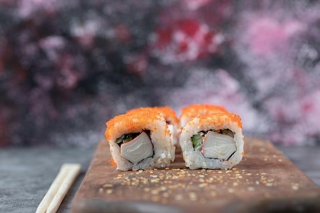 Sushi maki com caviar vermelho e cream cheese em uma placa de madeira.