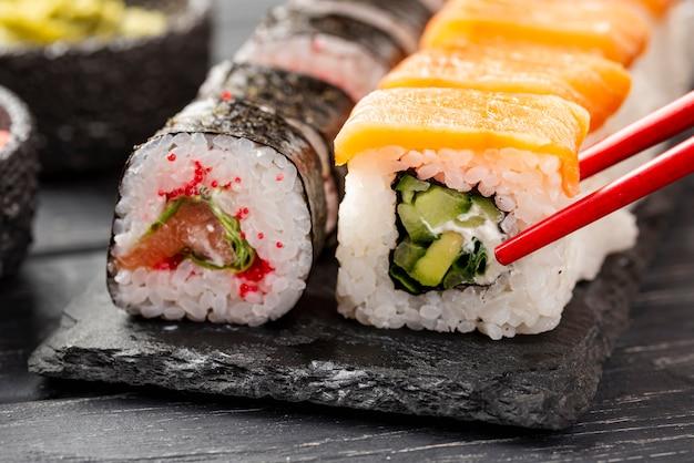 Sushi maki de close-up na ardósia com pauzinhos