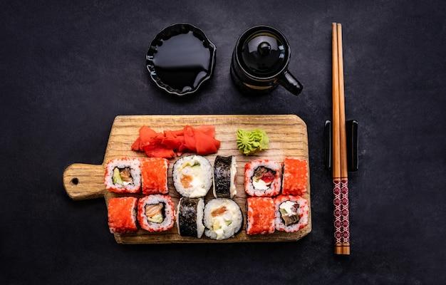 Sushi maki definido servido em um tablet de madeira com pauzinho e molho de soja na mesa preta lindos japoneses ...