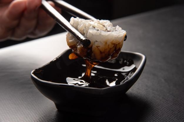 Sushi, mãos colhendo sushi usando hashi e mergulhando em molho tara