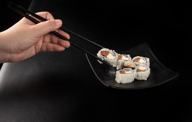 Sushi, mãos colhendo sushi usando hashi