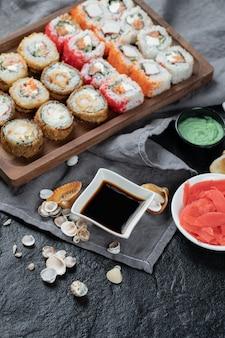 Sushi misto em uma placa de madeira com molho de soja à parte.